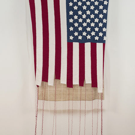 "image of Adrienne Sloane's ""The UnRaveling"" woven fiber American Flag with unraveling threads at the bottom"