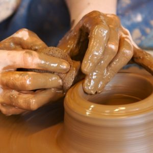 Hands forming a clay pot on the pottery wheel