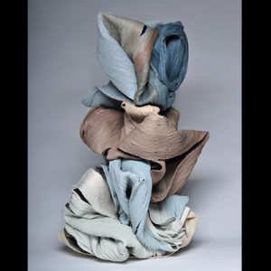 Ceramic piece mimics the texture of fabric, with multiple shades of pastel blue