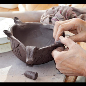 hands creating a clay bowl