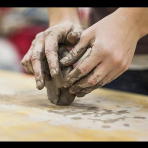 Hands sculpting fresh clay on a wooden board