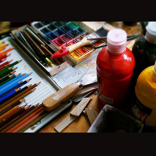 bottles of paint, colored pencils, and paint pallet, on a table