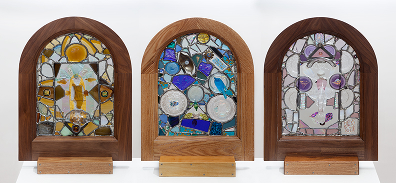Three glass windows that contain found objects such as earrings, pottery, and doll pieces.