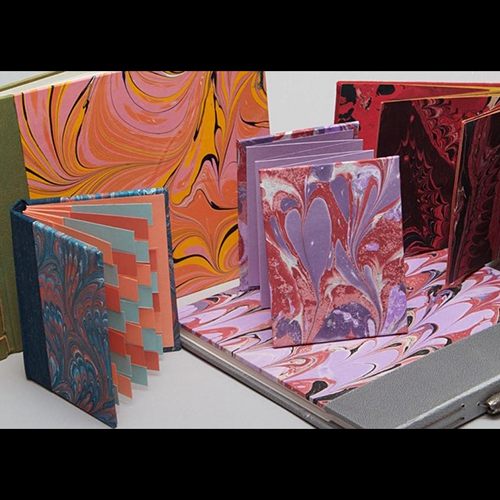 Books marbled with various colors including purples, oranges, and reds