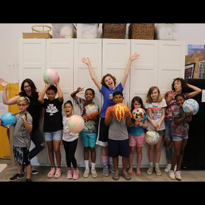 Children holding up colorful balloons