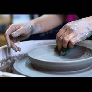 Hands sculpting a clay plate on the pottery wheel