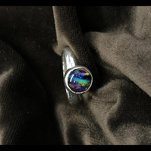 Silver ring with opalescent stone, on top of black fabric