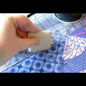 Quilting materials, including blue fabric, and a ruler