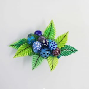 Blue polka dotted beads on top of bright green leaf shapes.