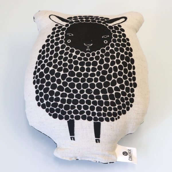 Pillow featuring a black and white sheep.