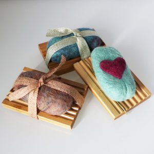 Three wool felted shea butter soaps in earth toned, blue toned, and a heart shaped design