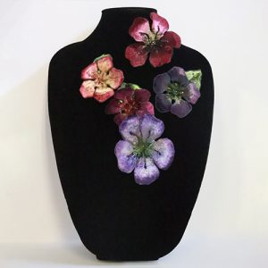 Textile floral pins in purple, red, and pink